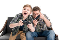 Father and son sitting on sofa and playing with joysticks. Isolated on white Royalty Free Stock Photo