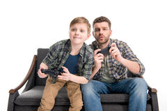 Father and son sitting on sofa and playing with joysticks Royalty Free Stock Photos