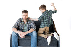 Father and son sitting on sofa and quarreling. Family problems concept Stock Photography