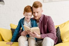 Father and son sitting on sofa and reading. Book together royalty free stock photography