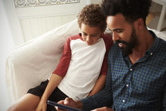 Father And Son Sitting On Sofa Using Digital Tablet Stock Photos