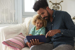 Father And Son Sitting On Sofa Using Digital Tablet Stock Images
