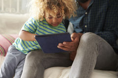 Father And Son Sitting On Sofa Using Digital Tablet stock image