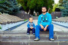 Father and son sitting on the stairs in the park Stock Image