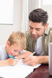 Father and son sitting at table colouring together. At home in kitchen Stock Photography