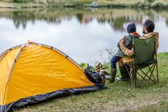 Father and son sitting at tent. Back view of father and son sitting in camping with tent at lake Royalty Free Stock Photo