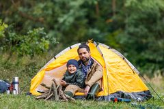 Father and son sitting in tent. Happy father and son sitting in tent in forest camping Royalty Free Stock Image