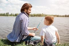 Father and son are sitting together on grass and looking at each other. Guy is holding fish-rod in hands. He is fishing. Bearded men is smiling royalty free stock photos