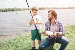 Father and son are sitting together on grass and looking at each other. Guy is holding fish-rod in hands. He is fishing. Bearded men is smiling royalty free stock images