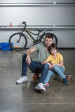 Father and son sitting together on skateboard in workshop Royalty Free Stock Photo