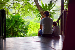 Father and son sitting on tree house stairs in tropical forest Royalty Free Stock Image
