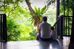 Father and son sitting on tree house stairs in tropical forest. Father and son sitting on the tree house stairs in tropical forest Stock Photography
