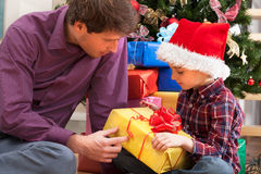 Father and son sitting under the christmas tree Royalty Free Stock Photography