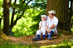 Father and son sitting under an old tree in forest Stock Photos