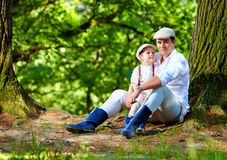 Father and son sitting under an old tree in forest Stock Images
