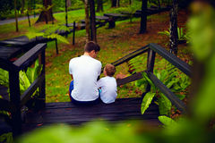 Father and son sitting on wooden stairs in rain forest Royalty Free Stock Images
