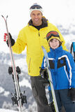 Father And Son On Ski Holiday In Mountains. Smiling Royalty Free Stock Photo