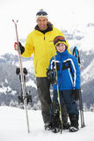 Father And Son On Ski Holiday In Mountains. Smiling At Camera Royalty Free Stock Photo