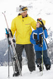 Father And Son On Ski Holiday In Mountains. Smiling At Each Other Stock Images