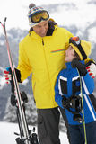 Father And Son On Ski Holiday In Mountains. Smiling At One Another Royalty Free Stock Image