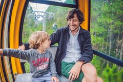 Father and son in ski lift cabin in summer. Passengers on a cable car Stock Images
