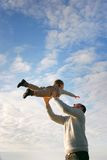 Father and son on sky background Royalty Free Stock Image