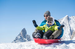 Father with son sledding. Father and son sledding during winter holiday. Happy dad and little boy playing with snow sled. Man with smiling child sitting on Stock Image