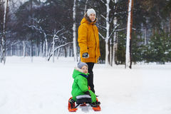Father and son sledding in winter park. Bright clothes Royalty Free Stock Photography