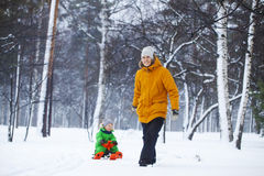 Father and son sledding in winter park. Father and son smilling and sledding in winter park. Bright clothes Royalty Free Stock Images