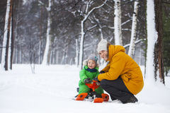Father and son sledding in winter park. Father and son smilling and sledding in winter park. Bright clothes. Snow on the trees Stock Image