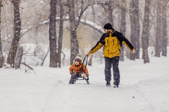 Father and son with a sledge outdoor in the snow stock photography