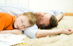 Father with son sleeping. Young father with his son sleeping on the carpet stock photo