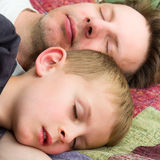 Father and Son Sleeping. On a colourful Quilt royalty free stock photo