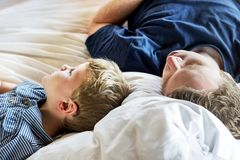 Father and son sleeping on a bed Stock Images