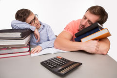 Father and son sleeping on books at the table Royalty Free Stock Images