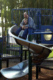 Father and Son on the Slide. A father and son on the slide at a playground Stock Photo