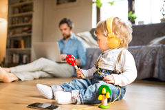 Father and son with smartphone, earphones and laptop. Royalty Free Stock Images