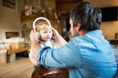 Father and son with smartphone and earphones, listening music. Unrecognizable young father at home with guitar, his little son wearing earphones and listening Royalty Free Stock Photos
