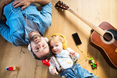 Father and son with smartphone and earphones, listening music. Young father and his little son with smart phone and earphones, listening music at home, lying on Royalty Free Stock Image