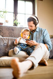 Father and son with smartphone and earphones, listening music. Royalty Free Stock Photography