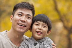 Father and son smiling in the park in autumn, close-up portrait Royalty Free Stock Image