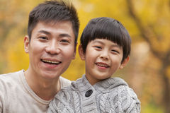 Father and son smiling in the park in autumn, close-up portrait Stock Images