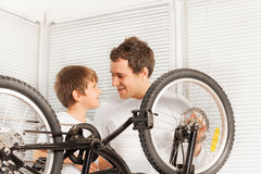 Father and son smiling together after fixing bike Royalty Free Stock Photos