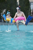 Father and son in snorkeling gear sitting by the edge of the pool and splashing Royalty Free Stock Image
