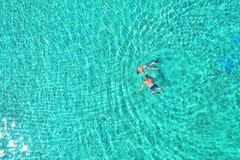 Father and son snorkels through tropical, turquoise waters, aerial view.  royalty free stock photos