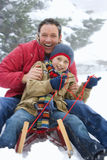 Father and son snow sledding Royalty Free Stock Photography
