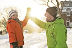 Father And Son In Snowy Landscape doing high five. A Father And Son In Snowy Landscape stock image