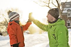 Father And Son In Snowy Landscape doing high five. A Father And Son In Snowy Landscape royalty free stock photo