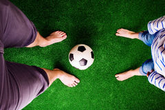 Father and son with soccer ball against green grass Royalty Free Stock Photography