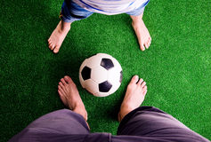 Father and son with soccer ball against green grass. Legs of unrecognizable father and son with soccer ball, against artificial grass. Studio shot on green royalty free stock images